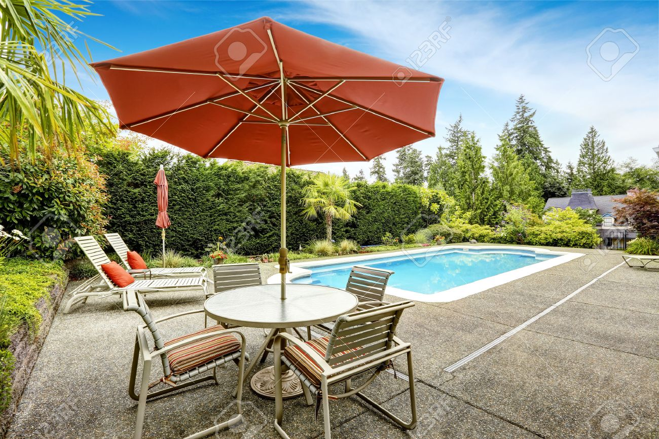 backyard with swimming pool deck chairs and patio table with
