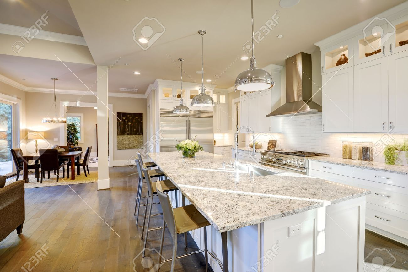 large white kitchen island stainless steel design features bar style stock photo with granite countertop illuminated by modern pendant lights northwest usa