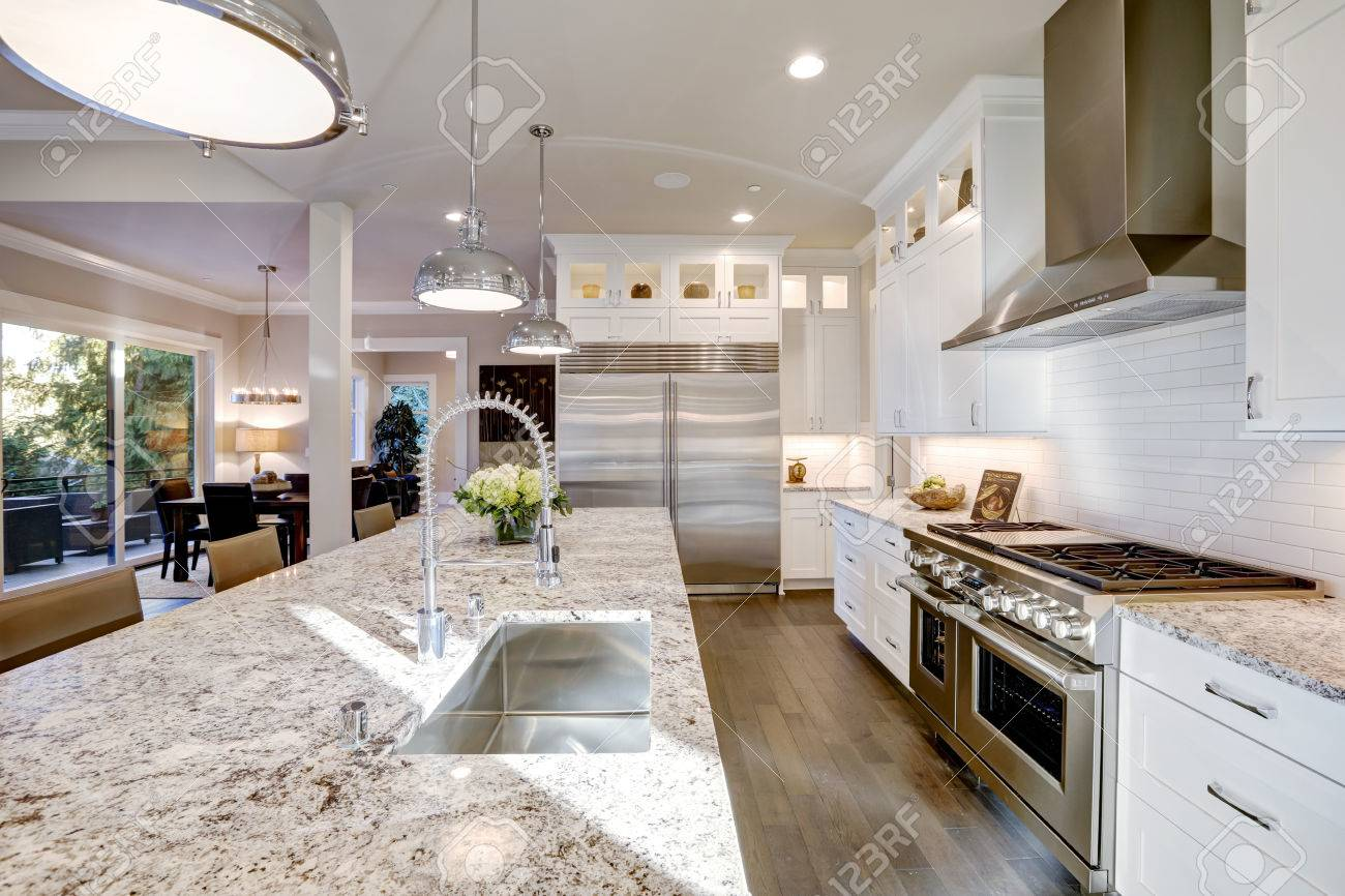 large white kitchen island sink drain pipe design features bar style stock photo with granite countertop illuminated by modern pendant lights