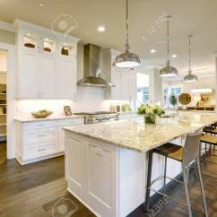 Large White Kitchen Island How To Build An Outdoor Design Features Bar Style Stock Photo With Granite Countertop Illuminated By Modern Pendant Lights