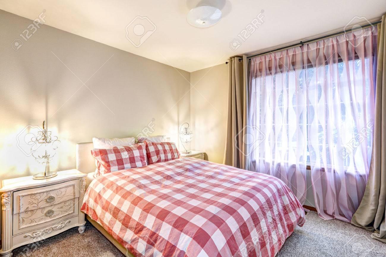 interieur belle chambre avec des murs beiges encadrant les fenetres habillees en taupe et rose rideaux aux cotes de lit recouvert de carreaux rouges et