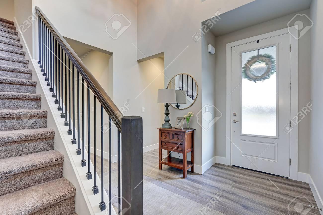 foyer gris avec revetement de sol stratifie haut plafond meuble avec console a cote de la porte d entree blanche et escalier avec garde corps en