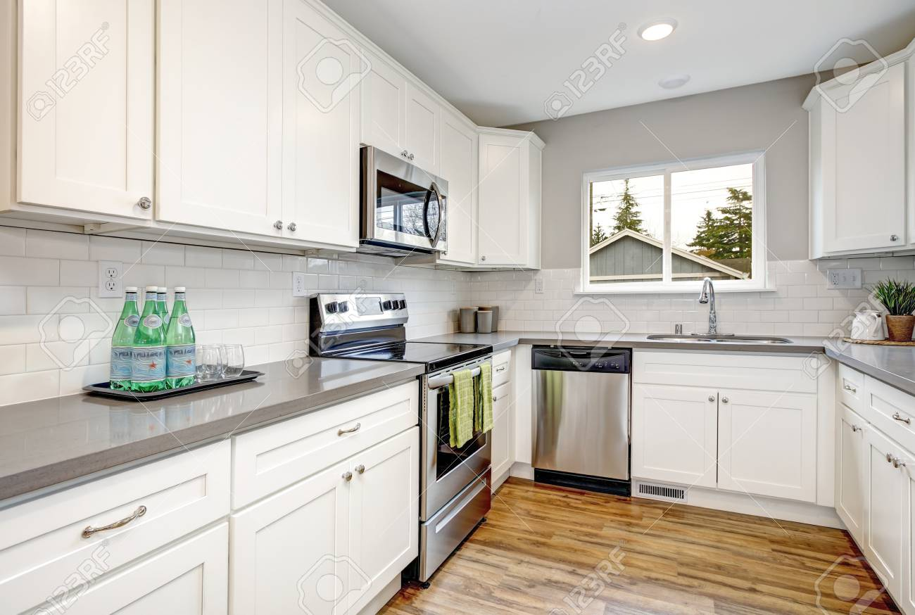 white and gray kitchen room with modern stainless steel appliances