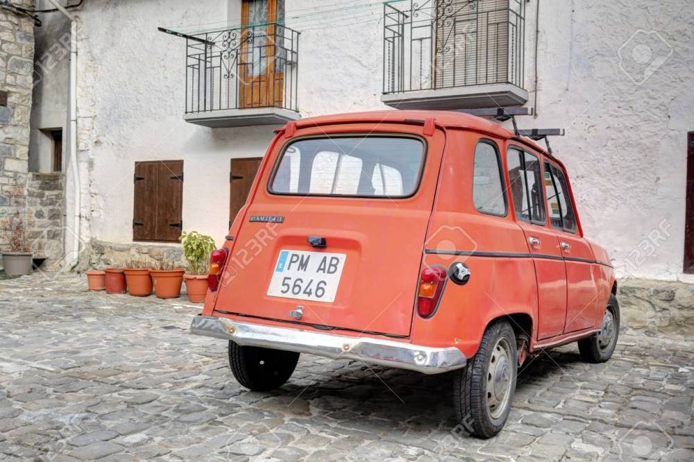 medium resolution of an old traditional renault 4 tl red car parked in the stone square of the rural