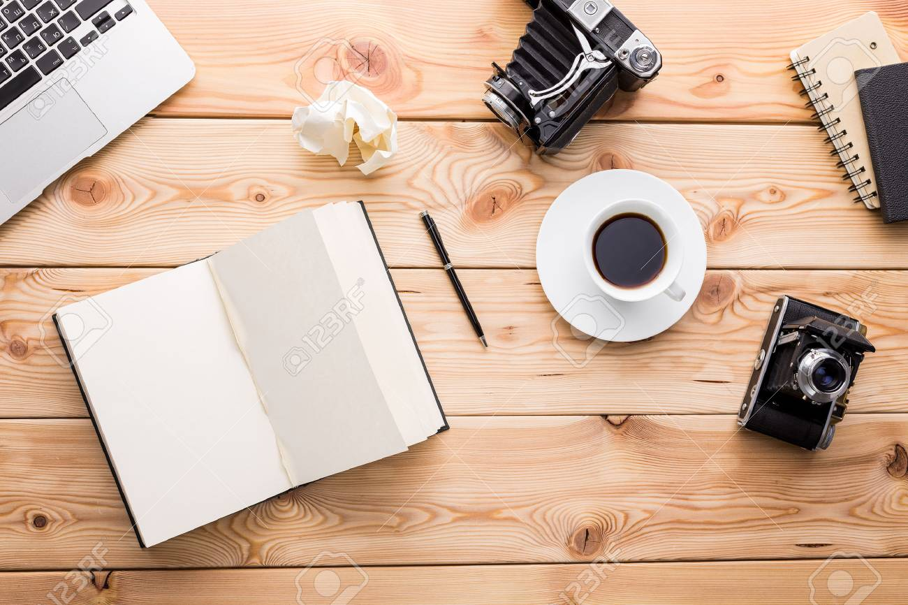 wooden table notebook vintage camera laptop and coffee on
