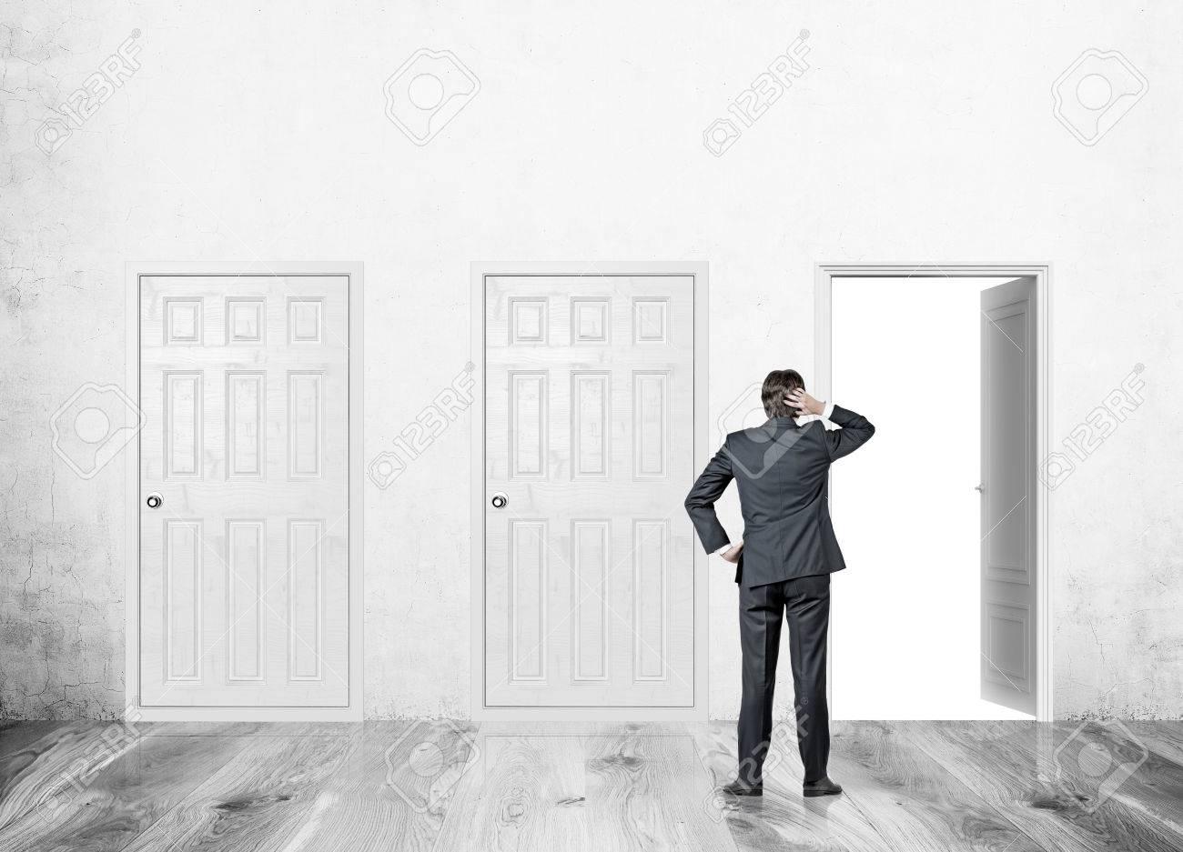 banque d images homme debout dans le couloir de mur de beton avec trois portes un ouvert deux fermes concept de trouver bonne facon de resoudre le
