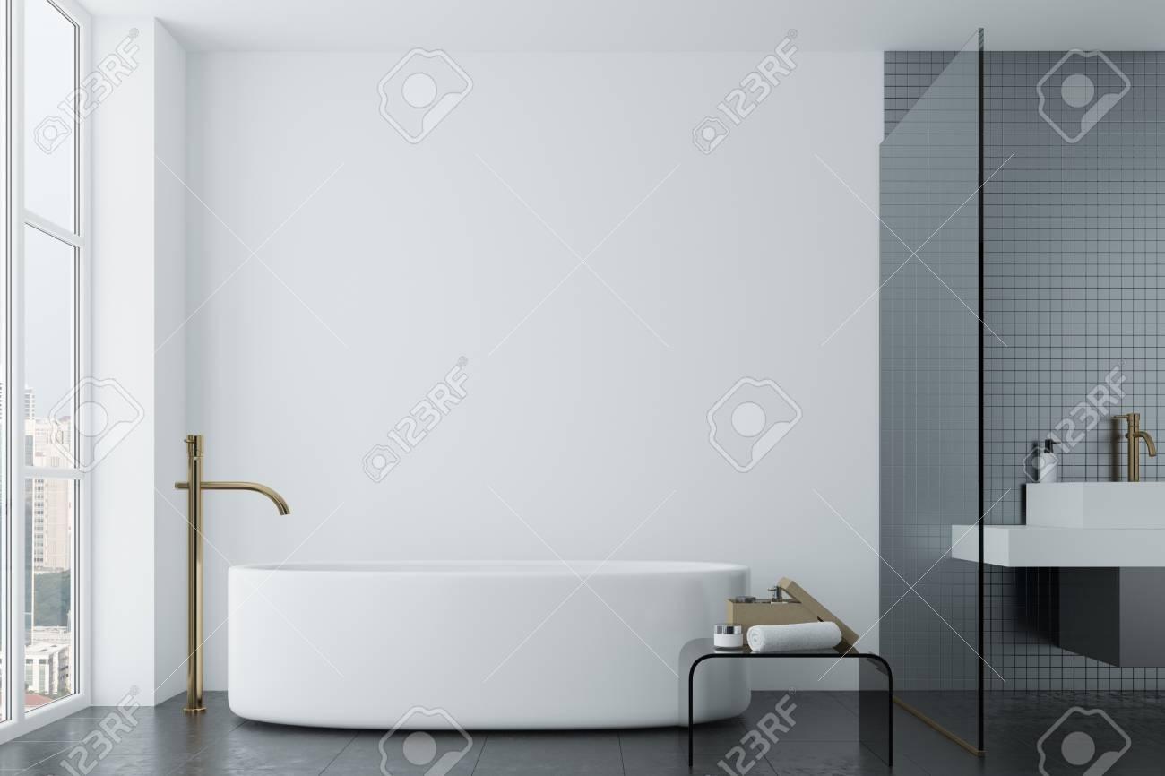 salle de bain loft blanc avec des carreaux gris fonce un lavabo angulaire et une baignoire ronde une petite table avec une serviette et un pot de