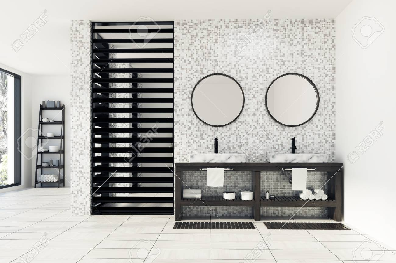 interieur de salle de bains en carrelage blanc et gris avec sol et murs blancs un double lavabo surmonte de deux miroirs ronds et une etagere avec