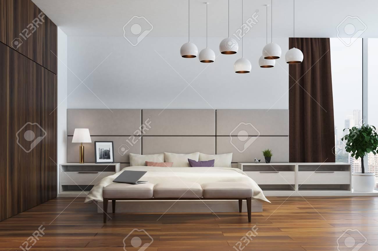 interieur de chambre a coucher blanc et beige avec un lit double plusieurs tables de chevet une armoire en bois et de grandes fenetres avec des