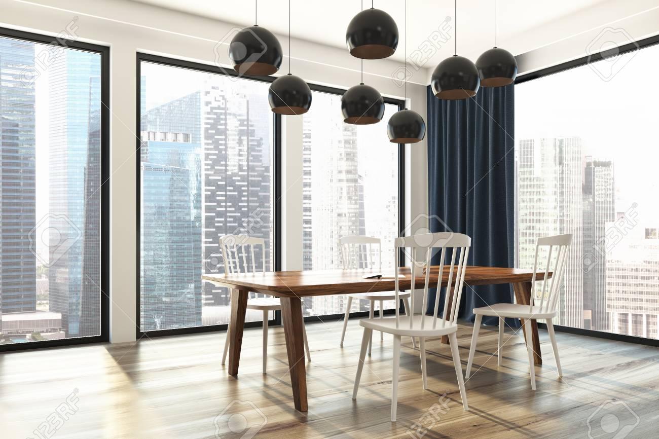 interieur de salle a manger blanc avec une grande fenetre avec des rideaux bleus une longue table en bois et des chaises blanches une vue de cote