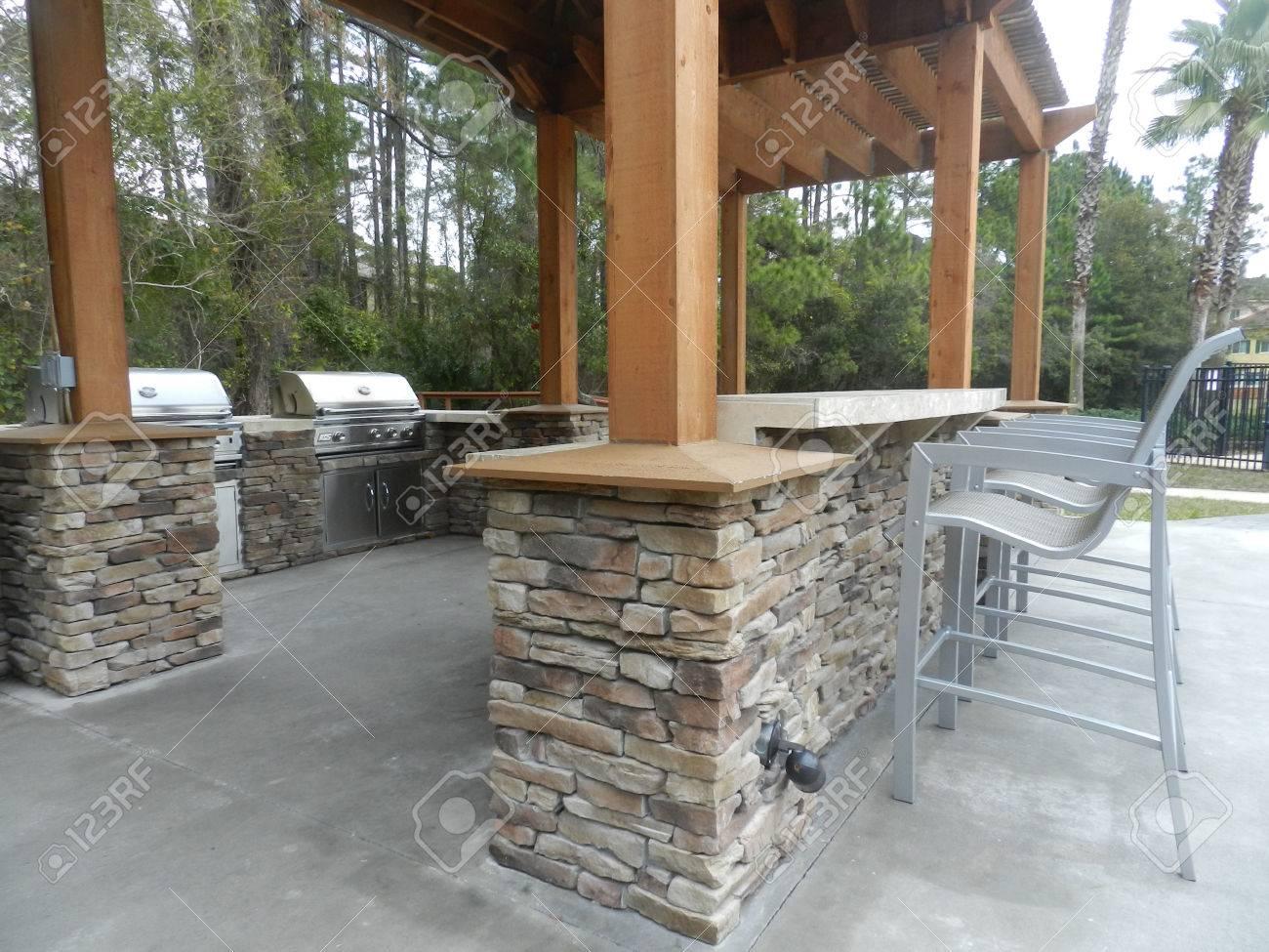 patio furniture with umbrellas on stone patio near upscale condo