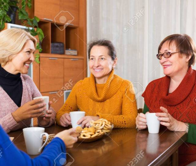 Mature Women Having Cup Of Hot Tea Indoor And Smiling Stock Photo