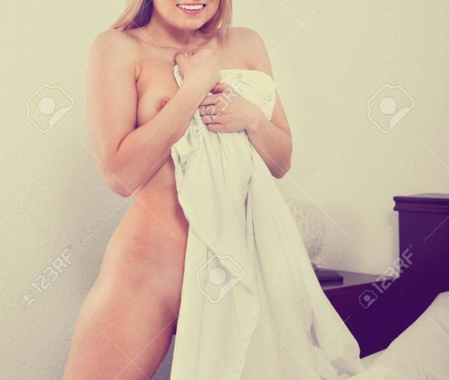 Cute Woman Without Clothes Standing And Covering Herself With A Sheet In The Bedroom Stock Photo