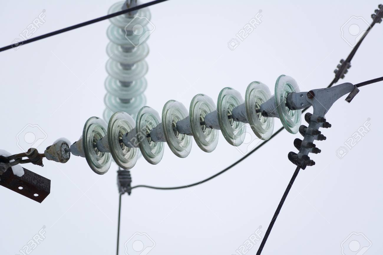 hight resolution of rows of electrical wires with insulators mounted on bars at high voltage electrical substation against blue