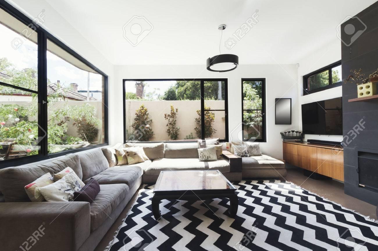 noir et blanc regime salon avec des accents de bois et de carrelage gris et chevron plancher de motif tapis