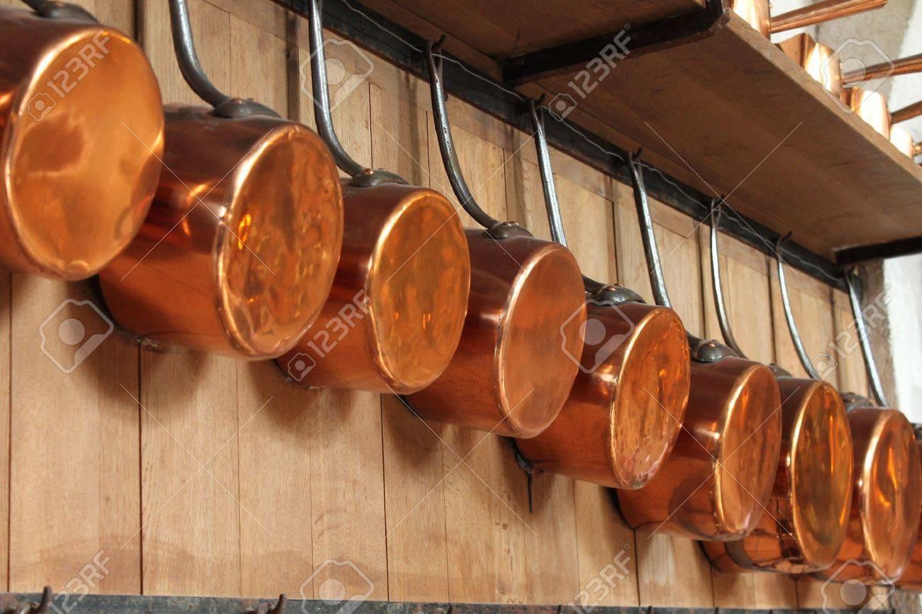 anciennes casseroles en cuivre a la main forge pendent d un mur dans une cuisine bien equipee pres de paris france