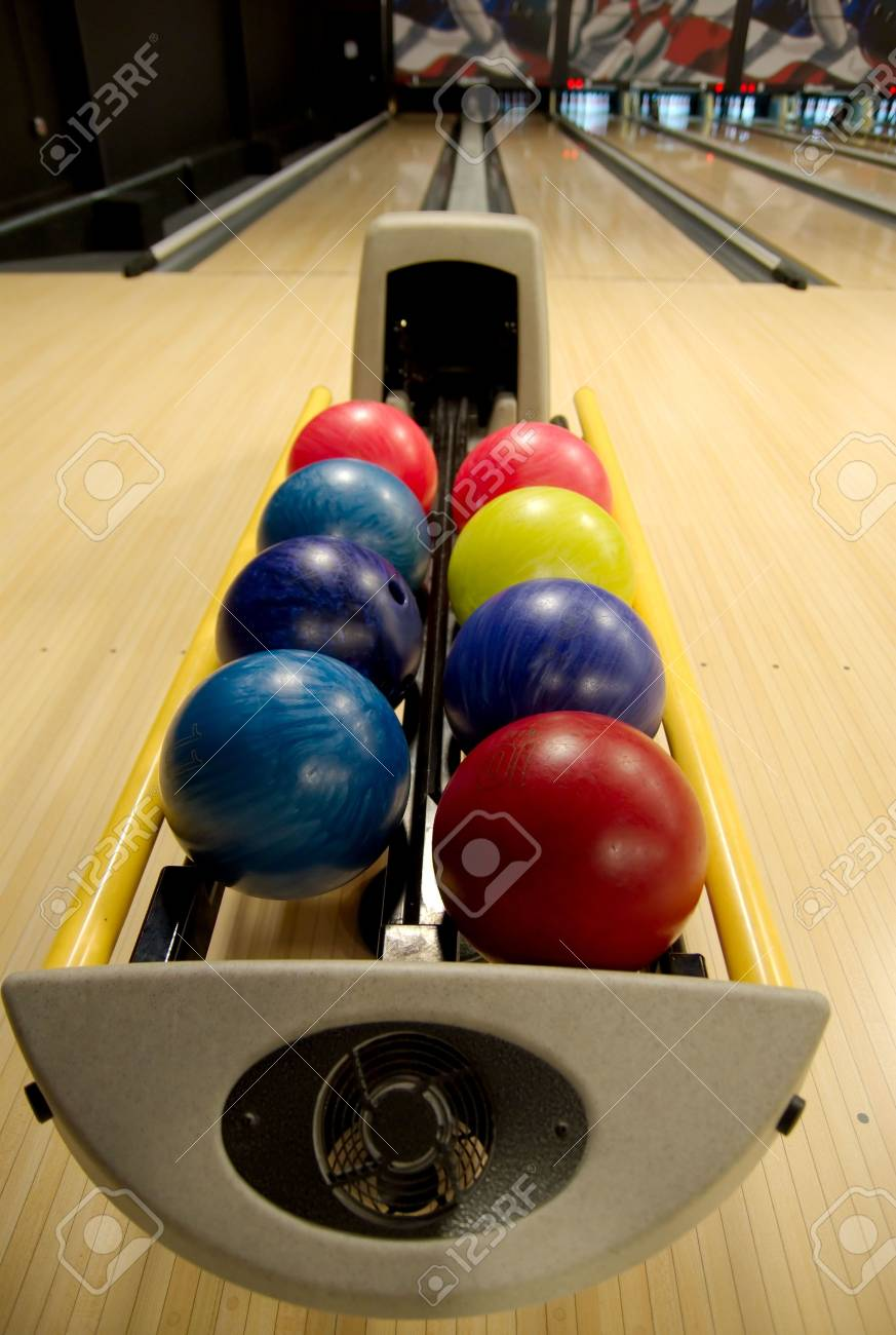 bowling balls in the rack at a bowling alley