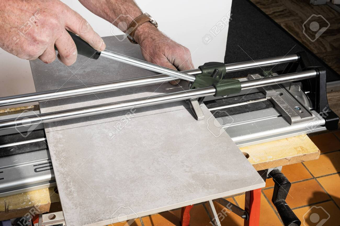 https www 123rf com photo 138081278 the mason cuts a ceramic tile with a tile cutter html