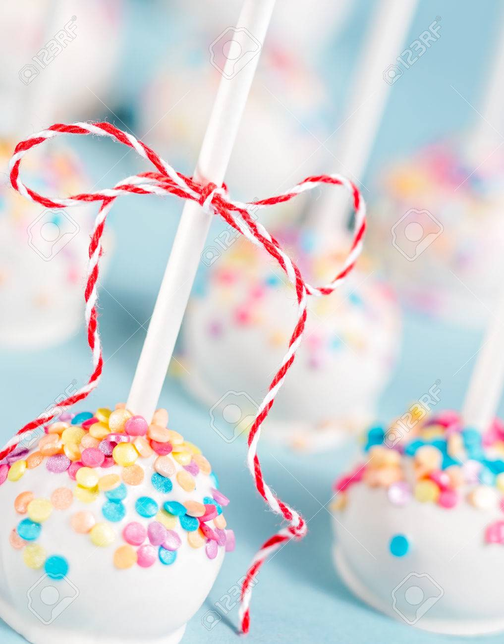 Vanilla Cake Pops With Colorful Sprinkles And Red Bow Over A Stock