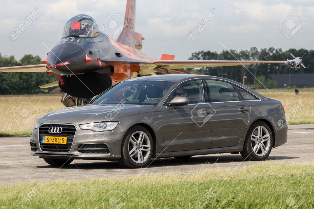 hight resolution of stock photo volkel netherlands jun 15 2013 audi a6 limousine driving in front of a dutch f 16 fighter jet during the royal netherlands air force open
