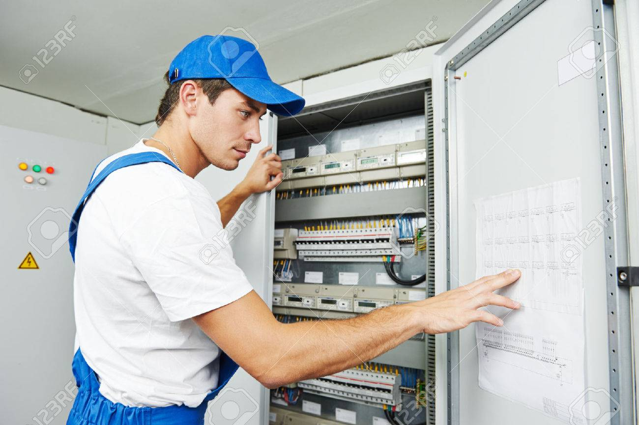 hight resolution of stock photo young adult electrician builder engineer inspecting electric counter equipment in distribution fuse box