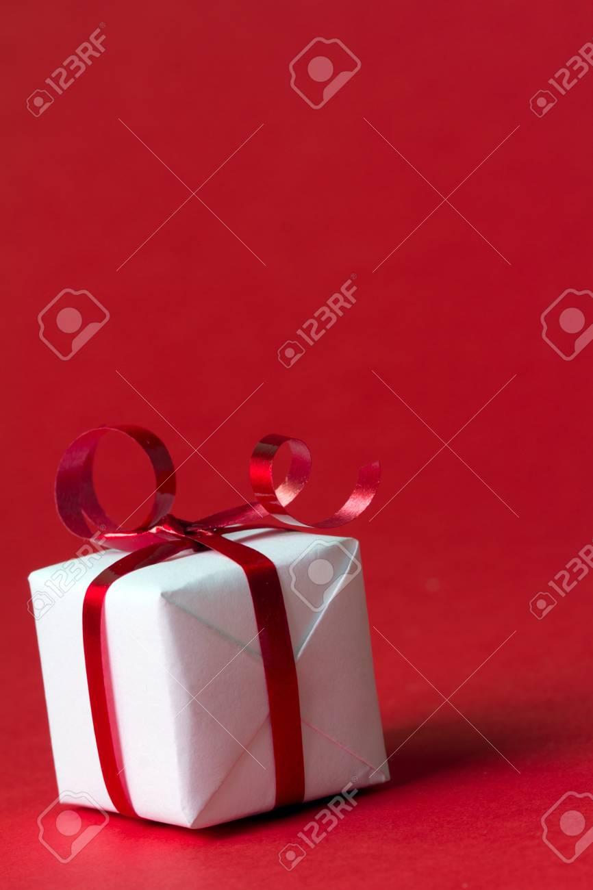 coffret cadeau blanc avec ruban rouge isole sur fond de couleur rouge