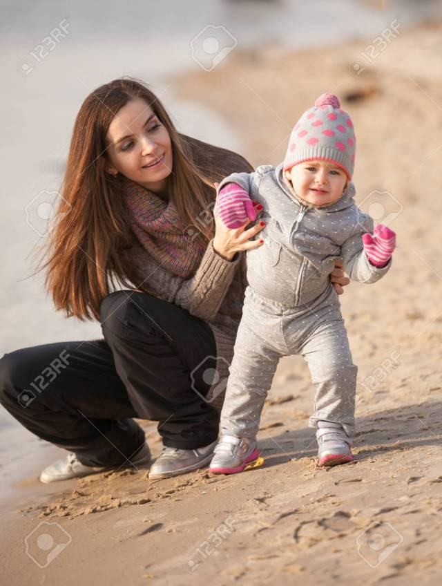 Stock Photo Young Brunette Mom Helping Small Daughter To Walk On Beach