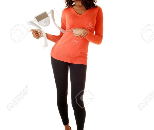 A Slim Tall Black Teen Girl Standing For White Background In The Studio Andholding A Scale In Her Hand