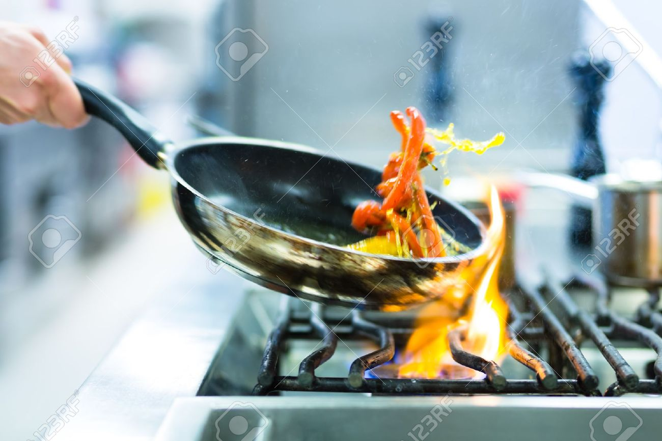 kitchen chief table sets chef in restaurant at stove with pan doing flambe on food stock photo