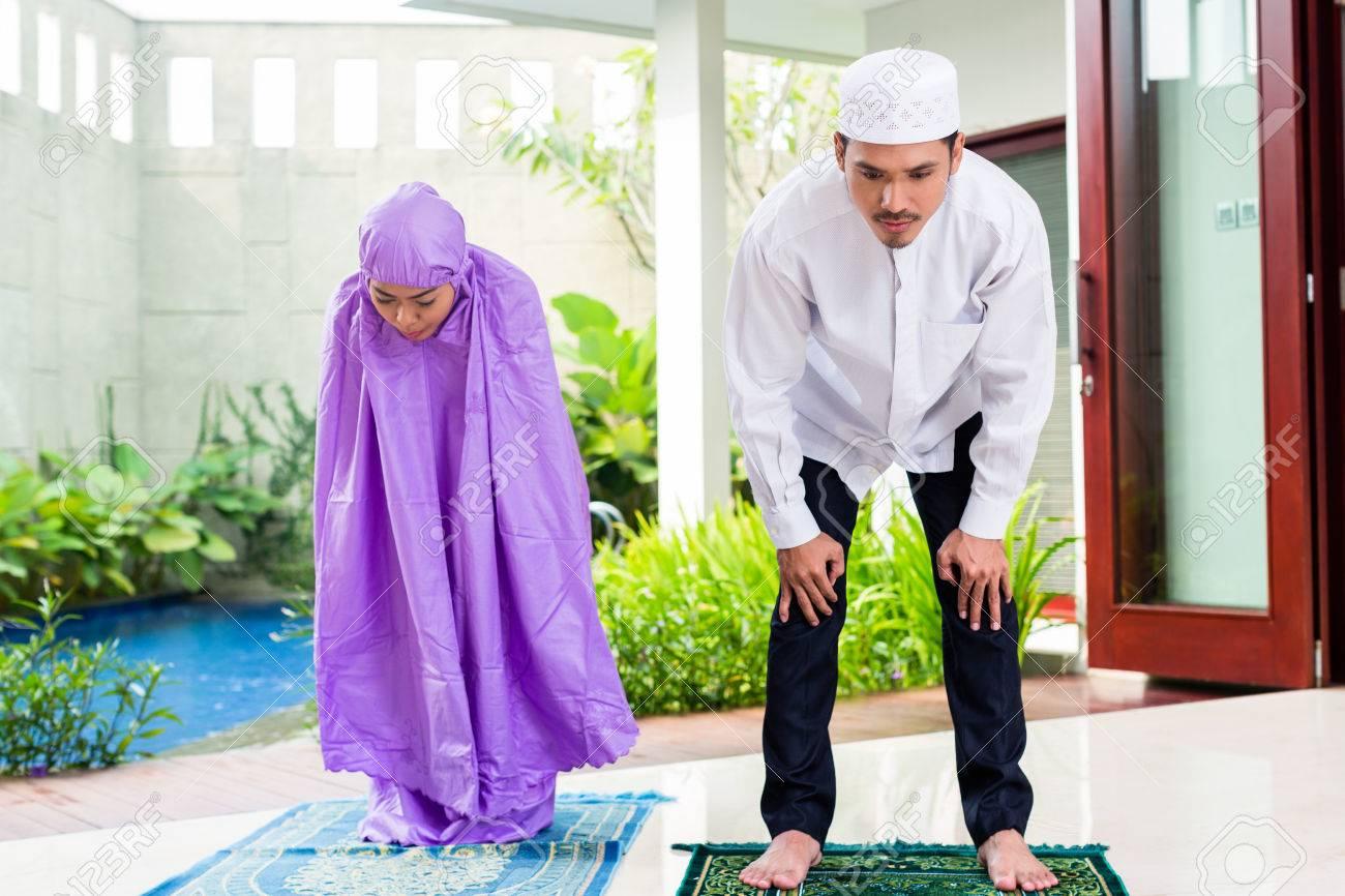 couple musulman asiatique homme et femme prier a la maison assis sur tapis de priere dans leur maison devant le jardin tropical