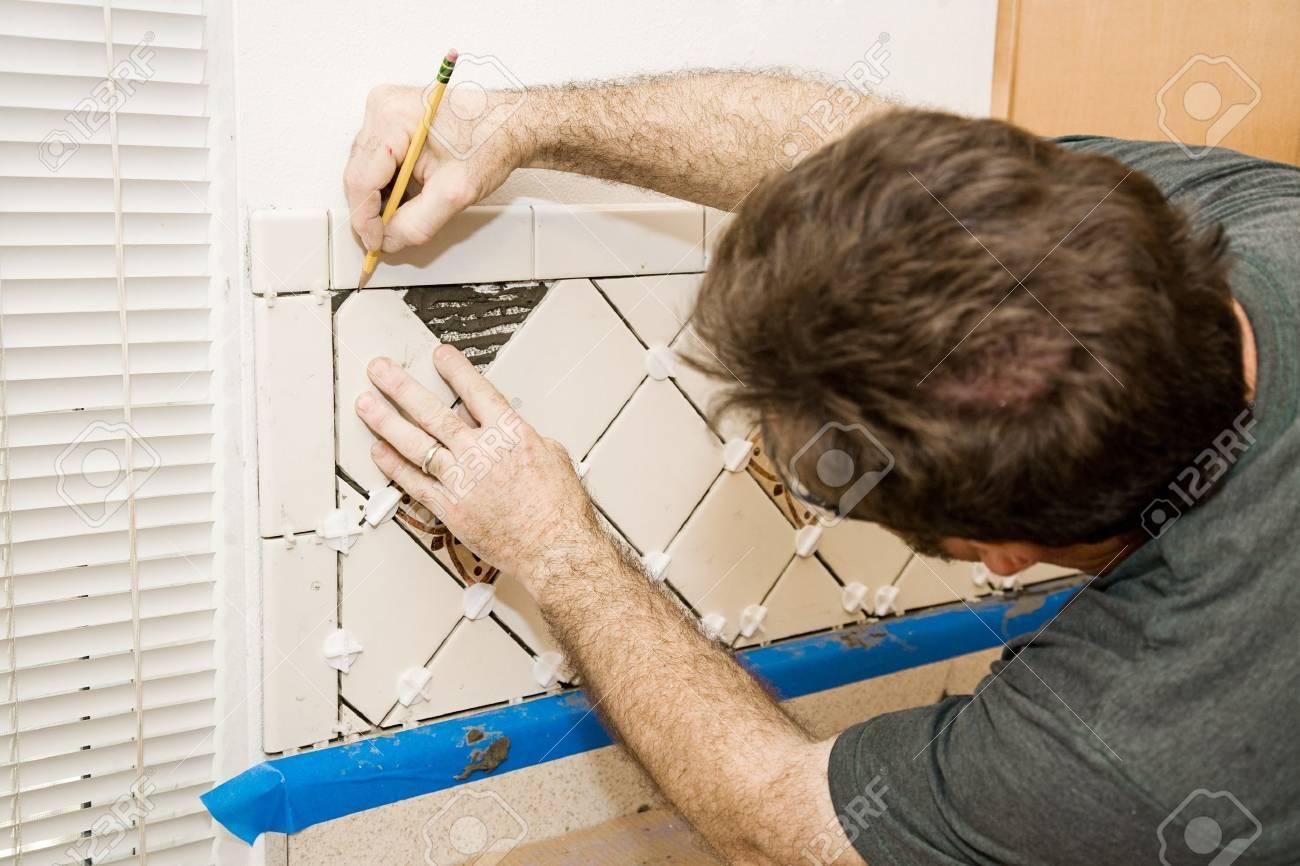 tile setter marking ceramic tiles for installation
