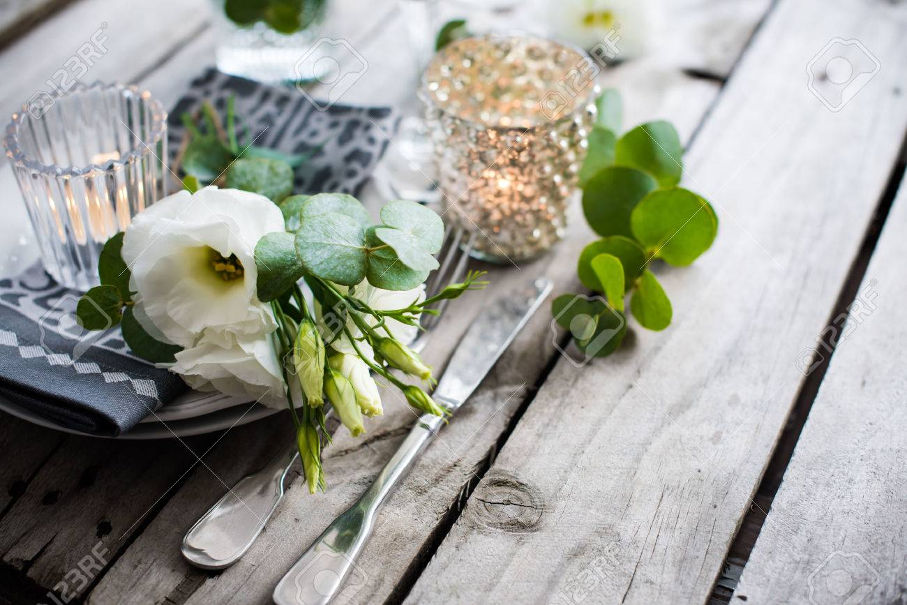 table decor with white flowers candles and glasses on old vintage