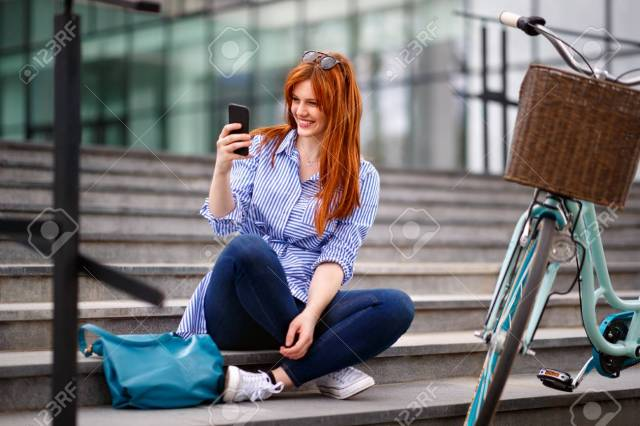 Stock Photo Young Smiling Woman Looking In Cell Phone While Resting On Stairs
