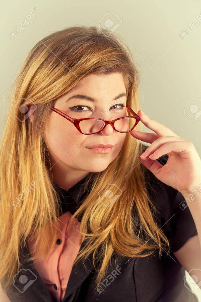 cute nerdy girl with reading glasses posing for a portrait