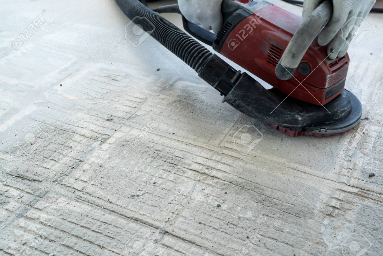 https www 123rf com photo 131235180 a construction worker uses a power concrete grinder for removing tile glue and resin during renovati html