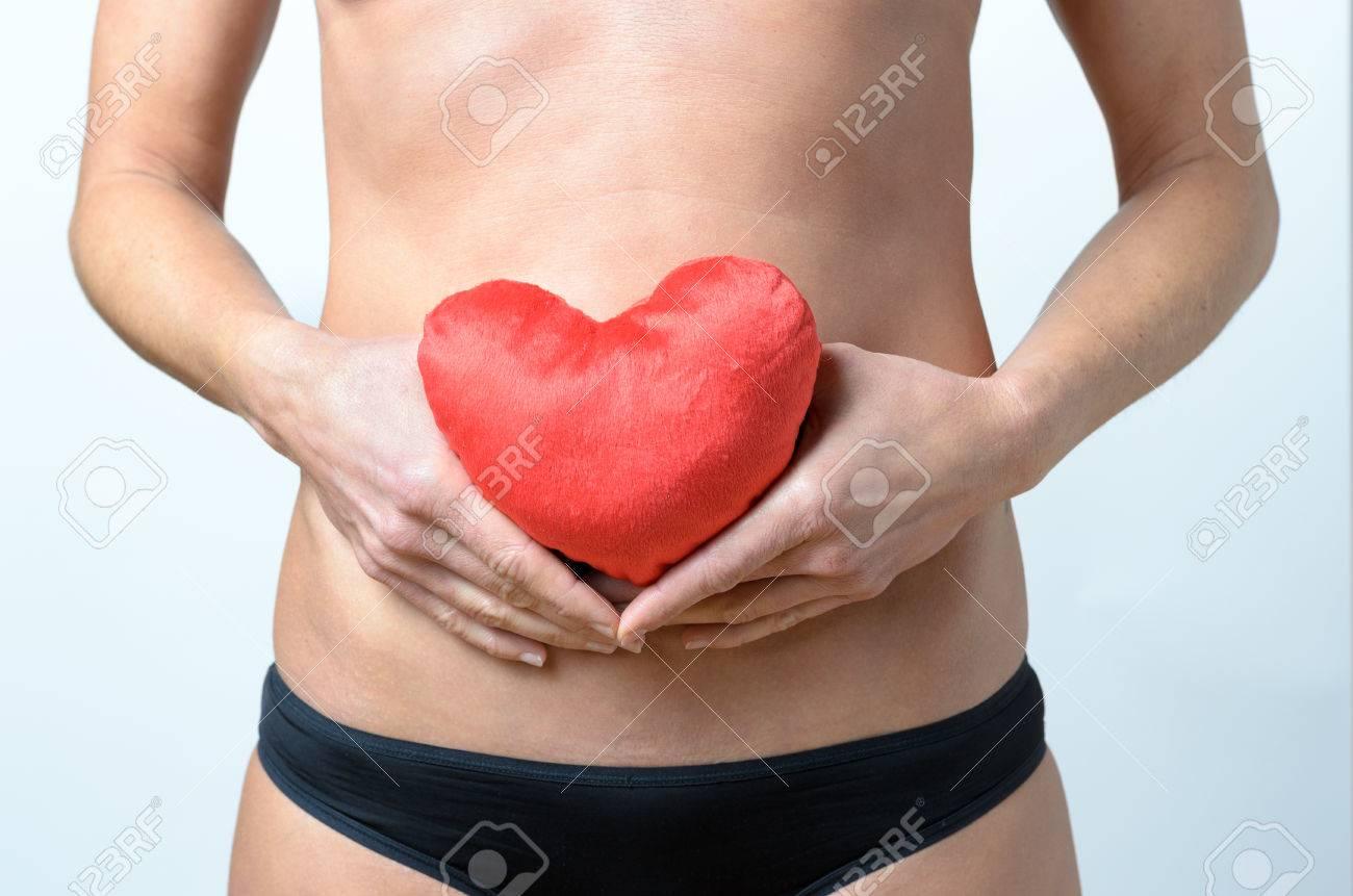 banque d images femme d age moyen tenant un oreiller qui ressemble a un coeur rouge devant son nombril gros plan