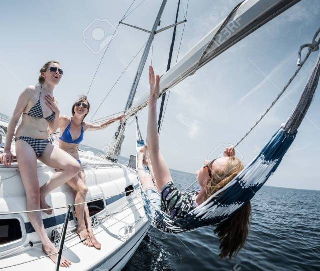 Lady Relaxing On The Sail Boat While Sailing In The Open Sea One Of Them