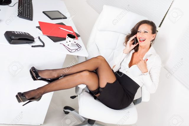 Sexy Business Woman Sitting On Office Chair And Talking On Mobile Phone Stock Photo