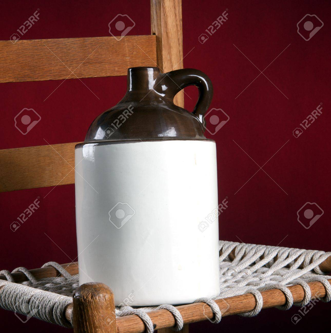 rope bottom chair inside swing an old pottery ceramic country jug and on a red background in the