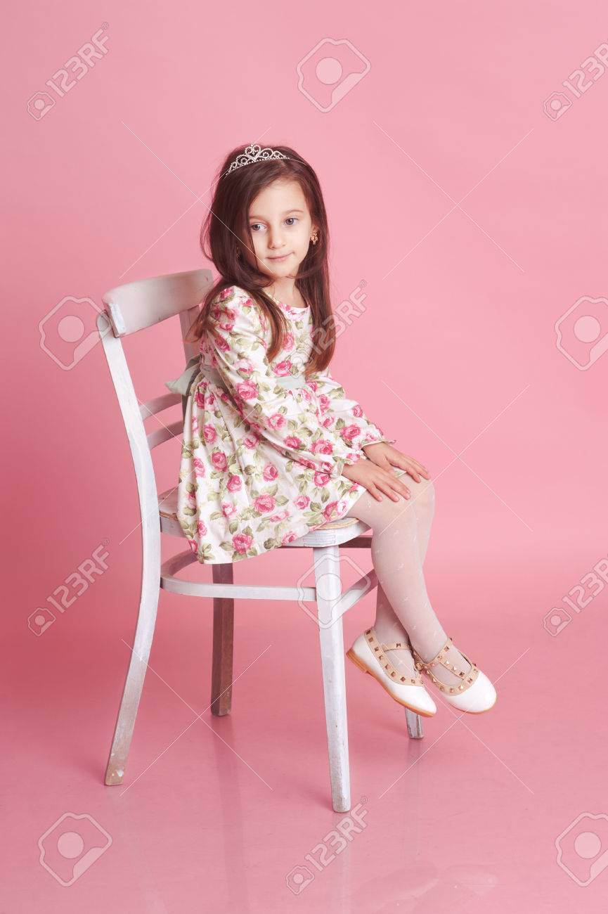 baby girl chair roll easy transport smiling 4 5 year old posing in studio over pink sitting on