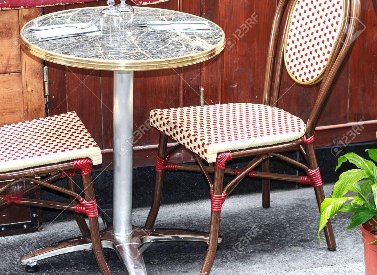 petite table ronde avec deux chaises rouges et blanches dans un cafe exterieur traditionnel a paris france