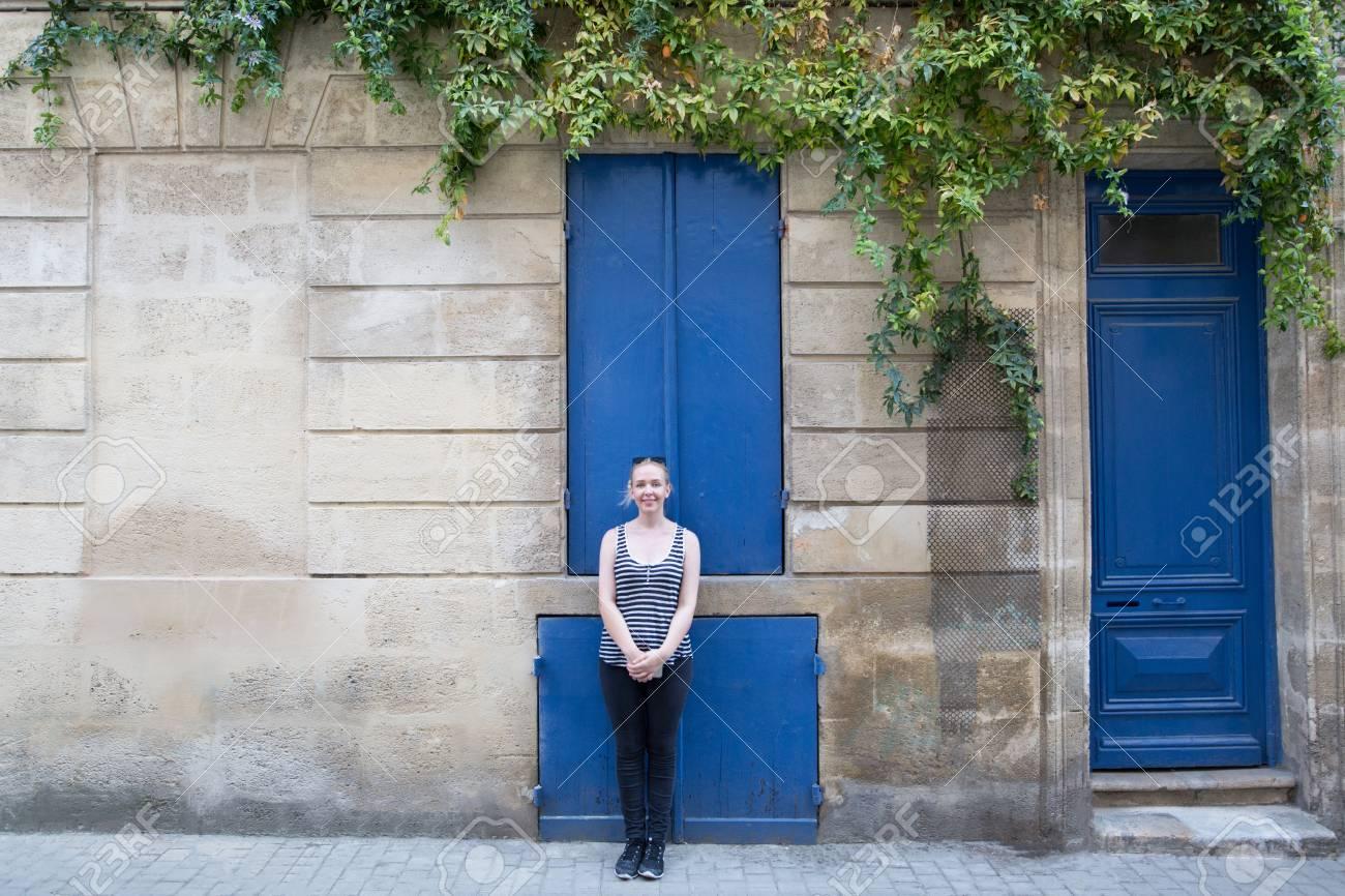 banque d images femme debout a cote de la fenetre et des portes de couleur bleue composition differente ivy sur le mur