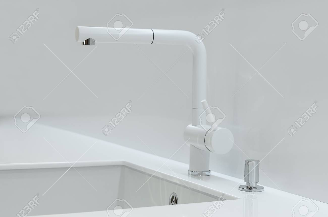 a new white kitchen sink made of artificial stone and a faucet