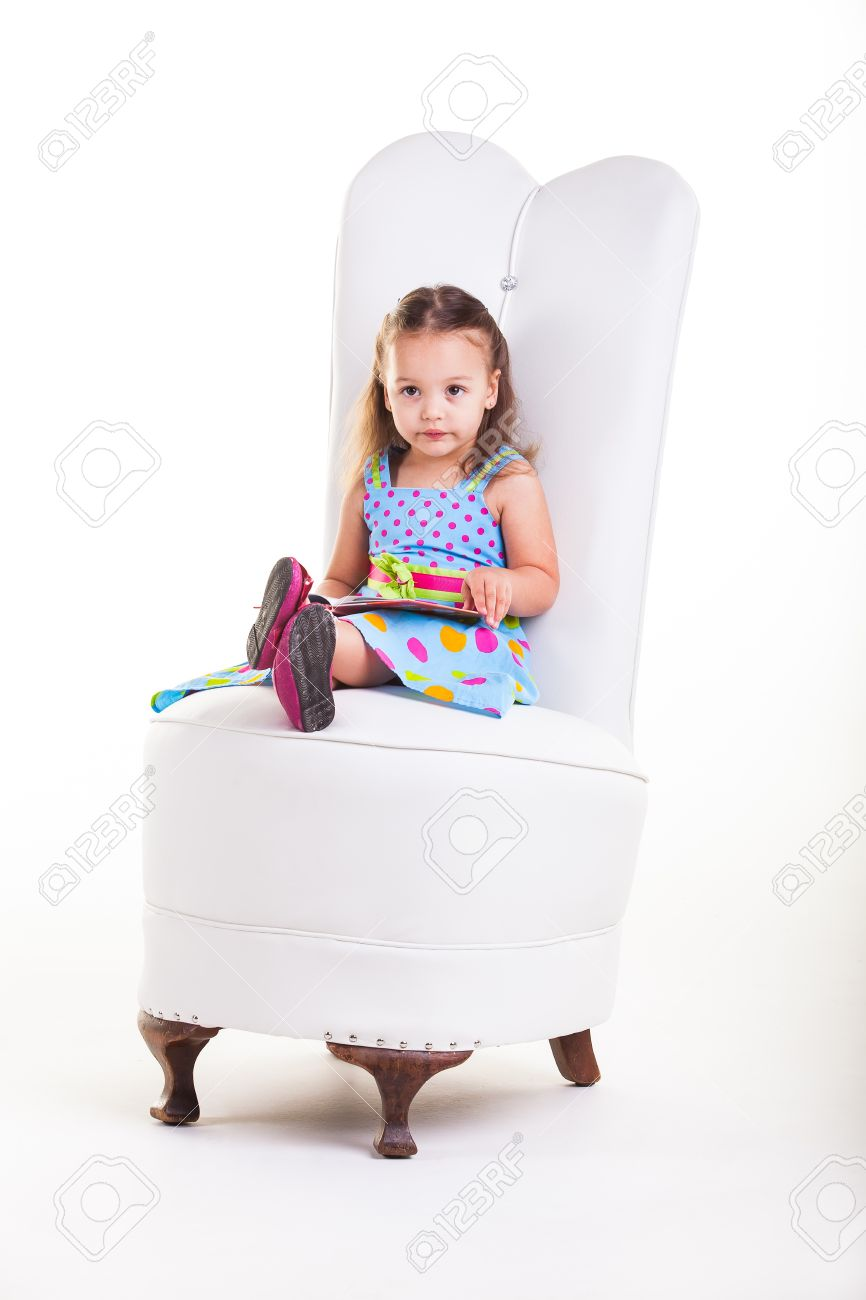 little girl chairs chair 1 2 covers a sitting on big reading her book stock photo 20078159