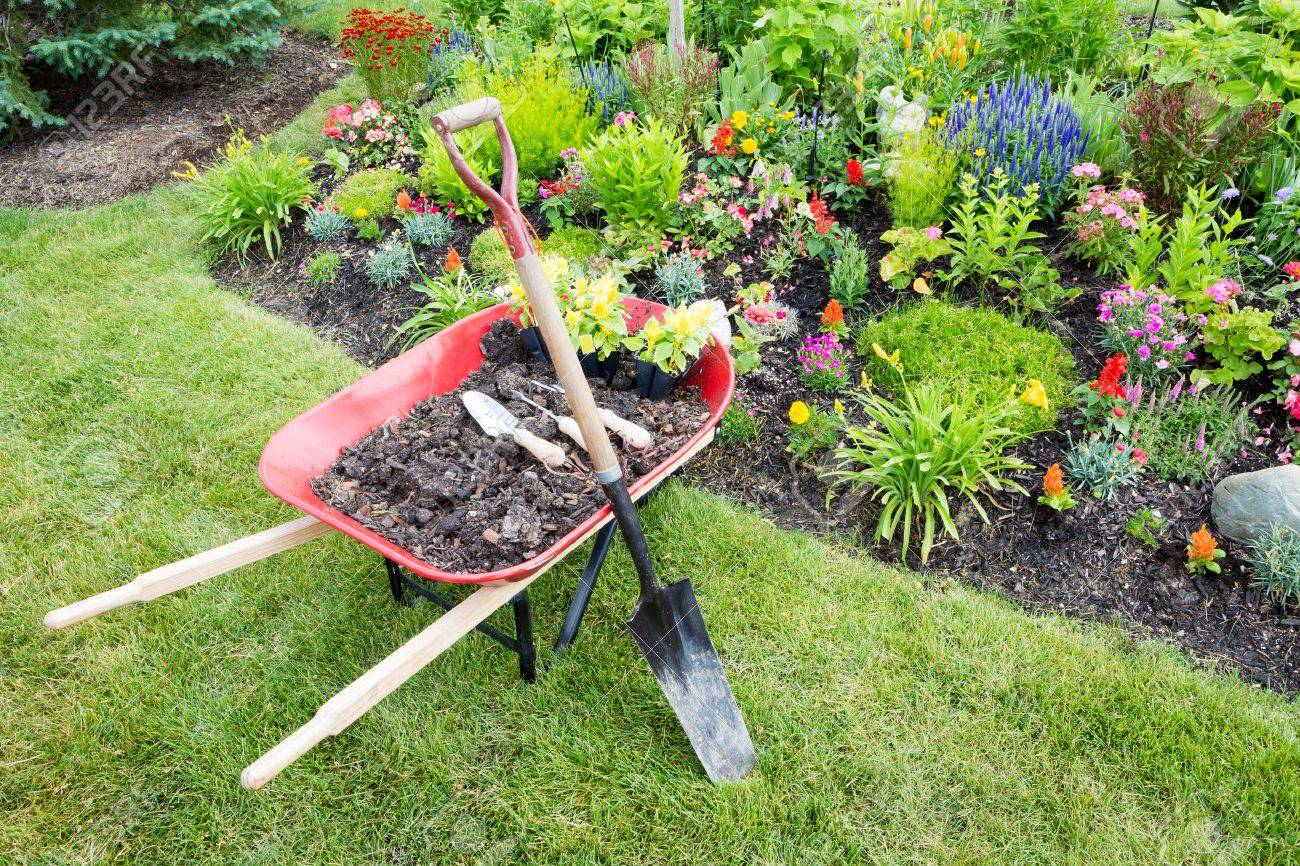 https://i0.wp.com/previews.123rf.com/images/oocoskun/oocoskun1406/oocoskun140600050/29237226-Garden-work-being-done-landscaping-a-flowerbed-with-a-red-wheelbarrow-full-of-organic-potting-soil-a-Stock-Photo.jpg