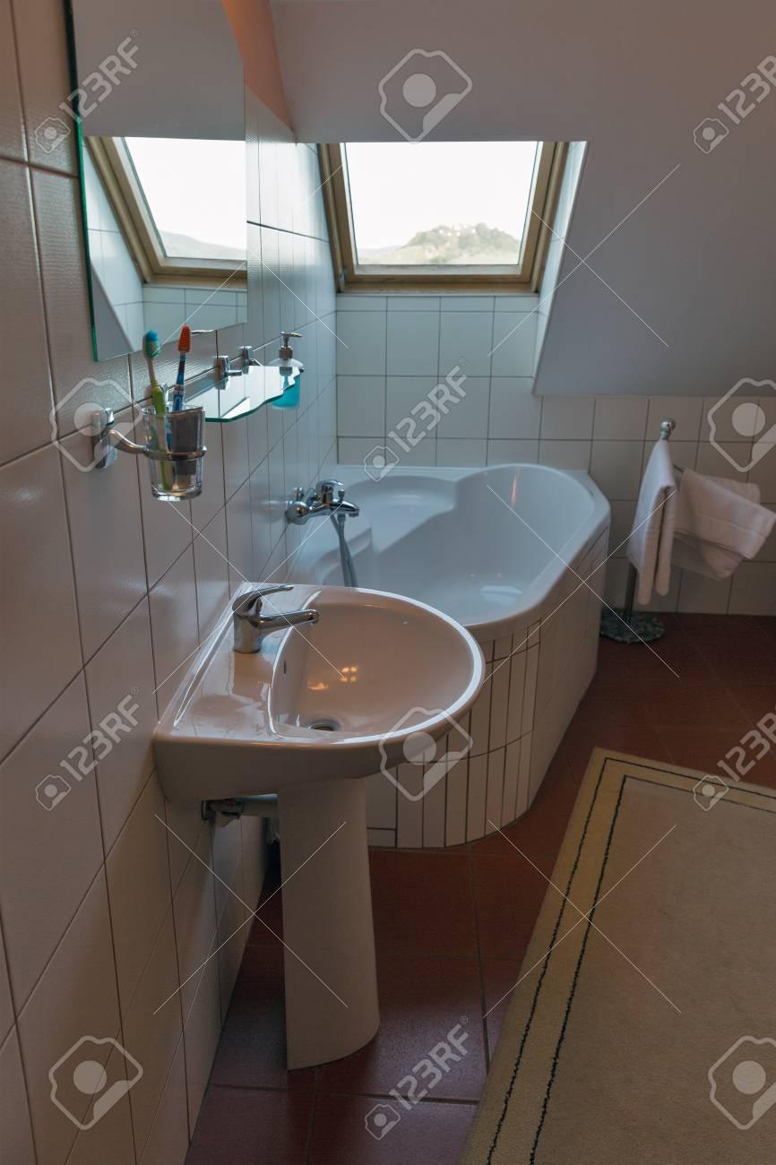 petite salle de bain blanche moderne avec baignoire d angle lavabo miroir et fenetre banska stiavnica slovaquie