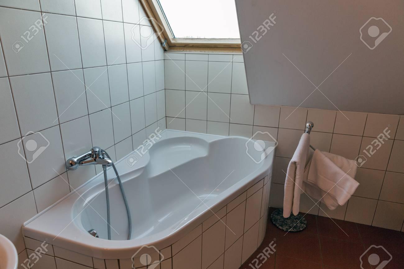 petite salle de bain blanche moderne avec baignoire d angle serviettes et fenetre