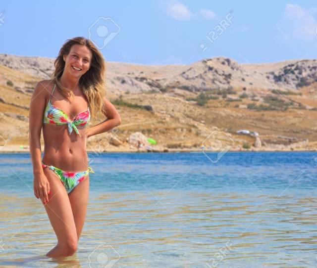 Beautiful Tanned Girl In A Bikini Standing In A Water Stock Photo