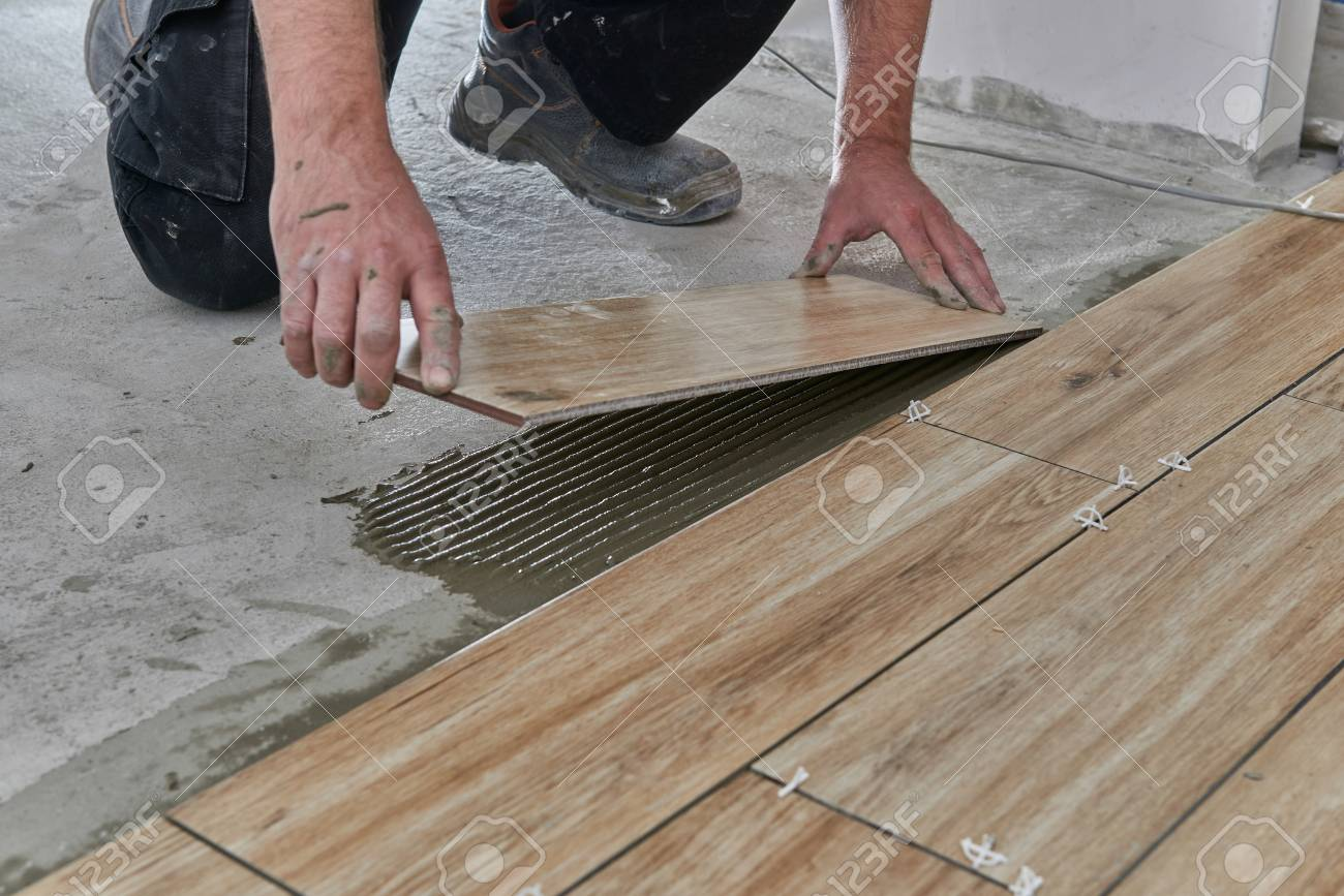 hands of the tiler are laying the ceramic wood effect tiles on stock photo picture and royalty free image image 120544067