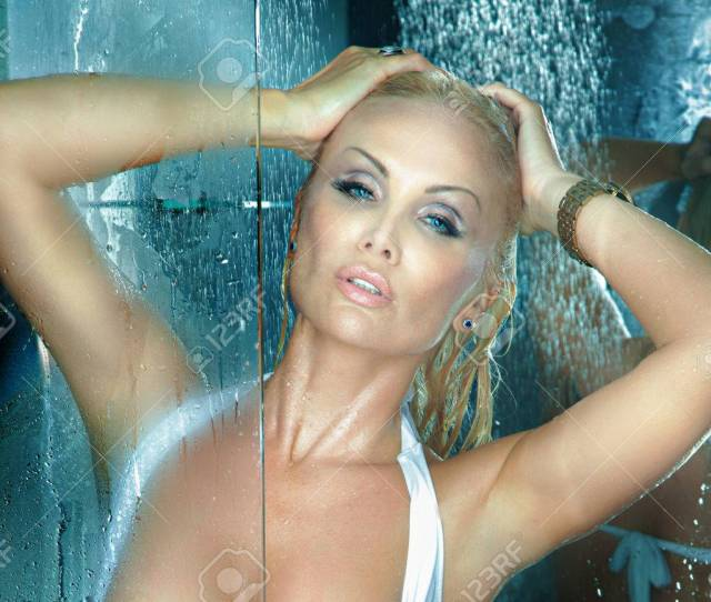 Portrait Of Beautiful Blonde Woman Taking Shower Looking At Camera Stock Photo
